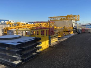 Picture of yellow crane rigging sitting on rig mats in a Grande Prairie yard.